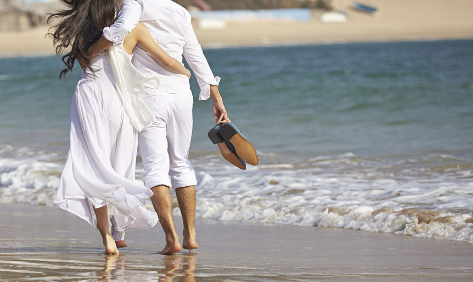 Couple-Walking-Barefoot-on-Beach